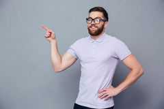Happy man in glasses pointing finger away Royalty Free Stock Image