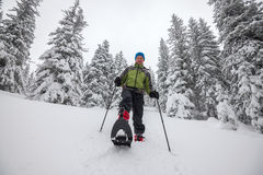 Happy man goes on snowshoes down the hill Royalty Free Stock Photography