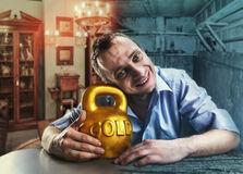 Happy man with a gold kettlebell. Happy man hugs a gold kettlebell in rich and poor home interior stock photography