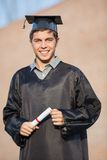 Happy Man In Graduation Gown Holding Certificate Royalty Free Stock Photography