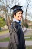 Happy Man In Graduation Gown On University Campus. Side view portrait of happy young man in graduation gown on university campus Royalty Free Stock Image
