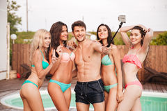 Happy man and group of women in swimsuits talking selfie Stock Photo