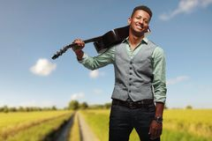 Young smiling hipster man posing joyfully with guitar on shoulder on blurred landscape background. royalty free stock photos