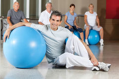 Happy man with gym ball in fitness. Happy men sitting with blue gym ball in fitness center with senior group Royalty Free Stock Photography