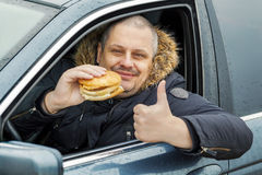Happy man with hamburger shows thumb up in the car. In winter day Stock Image