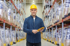 Happy man in hardhat with gloves over warehouse Stock Photo