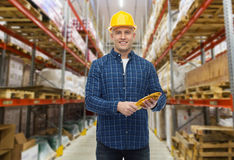 Happy man in hardhat with gloves over warehouse Royalty Free Stock Image
