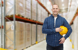 Happy man with hardhat over warehouse Stock Photos