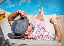 Happy man with a hat lying on a lounger Royalty Free Stock Photography