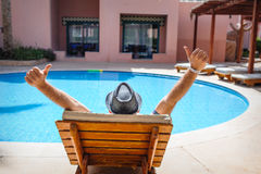 Happy man with a hat lying on a lounger Royalty Free Stock Images