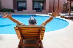 Happy man with a hat lying on a lounger by the pool Stock Photos