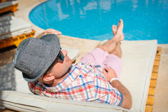Happy man with a hat lying on a lounger by the pool Stock Images