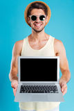 Happy man in hat and sunglasses holding blank screen laptop Stock Photos