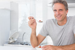 Happy man having cereal for breakfast in kitchen Royalty Free Stock Photos