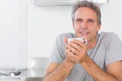 Happy man having coffee in kitchen Stock Image