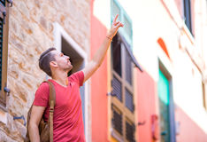 Happy man having fun during holidays in Cinque Terre. Young caucasian tourist walking at the old street. Smiling happy man having fun during holidays in Cinque Royalty Free Stock Photos