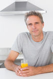 Happy man having glass of orange juice in kitchen Royalty Free Stock Photo