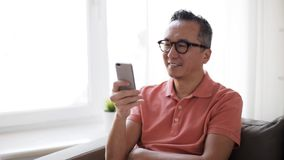 Happy man having video call on smartphone at home stock footage