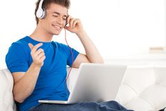 Happy man in headphones with laptop relaxing on sofa at home. Royalty Free Stock Photos