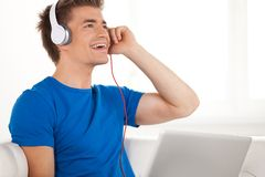 Happy man in headphones with laptop relaxing on sofa at home. Royalty Free Stock Image