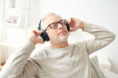 Happy man in headphones listening to music at home. Technology, people and lifestyle concept - happy senior man in headphones listening to music at home stock image
