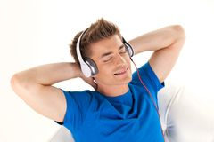 Happy man in headphones relaxing on sofa at home. Stock Images