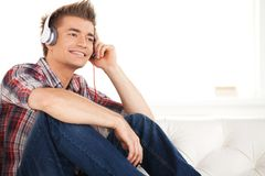 Happy man in headphones relaxing on sofa at home. Royalty Free Stock Photo