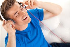 Happy man in headphones relaxing on sofa at home. Stock Photography
