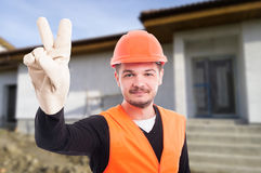 Happy man with helmet showing two fingers. As victory sign outside at workplace Stock Photos