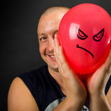 Happy man hiding behind angry balloon. Happy man hiding behind red balloon with angry smiley Stock Photography