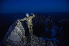 Happy man hiker celebrates success at mountain top in winter evening.  Royalty Free Stock Image