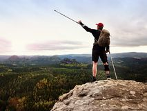 Happy man hiker holding medicine crutch above head, injured knee fixed in knee brace feature royalty free stock photos