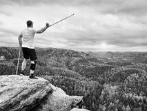 Happy man hiker holding medicine crutch above head, injured knee fixed in knee brace feature Royalty Free Stock Images