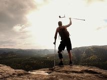 Happy man hiker holding medicine crutch above head, injured knee fixed in knee brace feature. Scenic mountain top with deep misty valley bellow royalty free stock photo