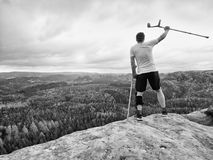 Happy man hiker holding medicine crutch above head, injured knee fixed in knee brace feature Stock Photos