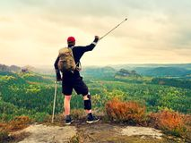 Happy man hiker holding medicine crutch above head, injured knee fixed in knee brace feature Stock Images