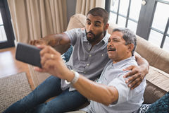 Happy man with his father taking selfie at home. Happy men with his father taking selfie while sitting together on couch at home Stock Photos