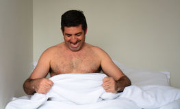 Happy man in his forties (40s) in bed looking down at his penis Royalty Free Stock Photo