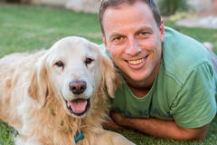 Happy man with his Golden Retriever dog both looking at the camera. Happy man with his Golden Retriever dog both looking at the camera and laying down on the Royalty Free Stock Photo