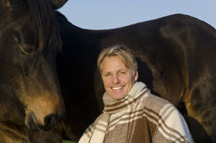 Happy man with his horse. A color portrait photo of a handsome smiling mature man in his forties with blonde hair sitting with his horse Royalty Free Stock Image