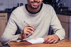 Happy man is in his kitchen keeping a diary Royalty Free Stock Photos