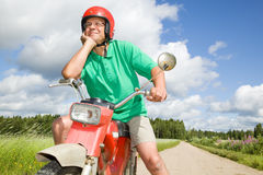 Happy man with his moped. In countryside Stock Image