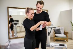 Happy man and his personal trainer looking at ems printout. Portrait of happy men and his personal trainer looking at ems printout royalty free stock photo