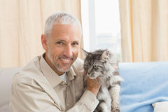 Happy man with his pet cat on sofa Royalty Free Stock Photos
