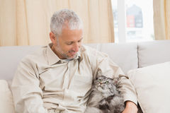 Happy man with his pet cat on sofa Royalty Free Stock Photo
