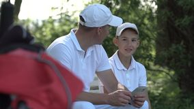 Happy man with his son golfers walking on perfect golf course at summer day stock video footage