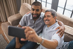 Happy man with his son taking selfie at home. Happy men with his son taking selfie while sitting together on couch at home Stock Images