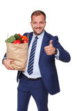 Happy man hold bag with healthy food, grocery buyer isolated. Smiling young businessman hold shopping bag full of groceries isolated at white background. Healthy royalty free stock photography
