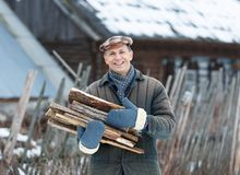 Happy man holding an armful of firewood Royalty Free Stock Photography