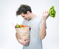 Happy man holding a bag full of groceries. Over gray background Stock Image